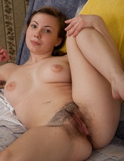 Horny Silviya seductively strips out of her skirt and yellow stockings on the sofa. She lays her gorgeous body back, and finger bangs her sexy hairy pussy.